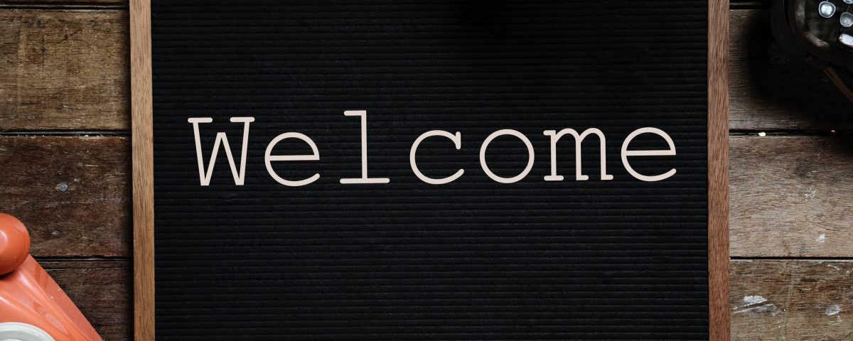 "A black sign with white lettering that reads ""Welcome"""
