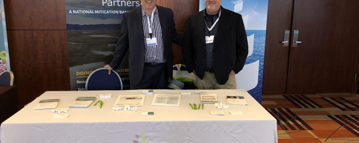 Two men stand in front of two banners and behind a conference table with various swag laid out on top of the table.