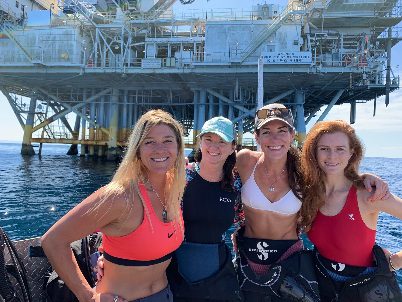 Four women in scuba gear, on a boat, in front of an oil rig