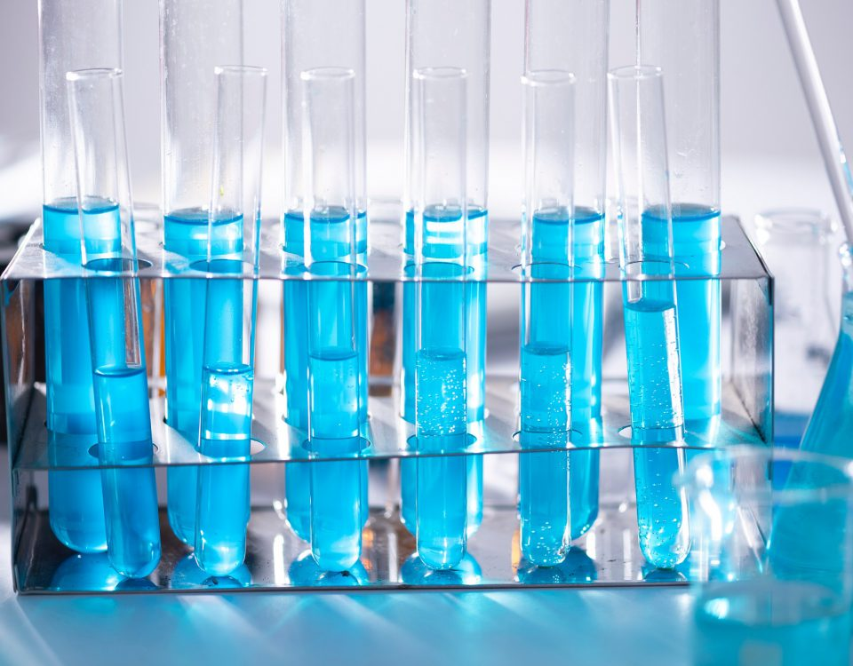 Vials of blue liquid are lined up on a lab table