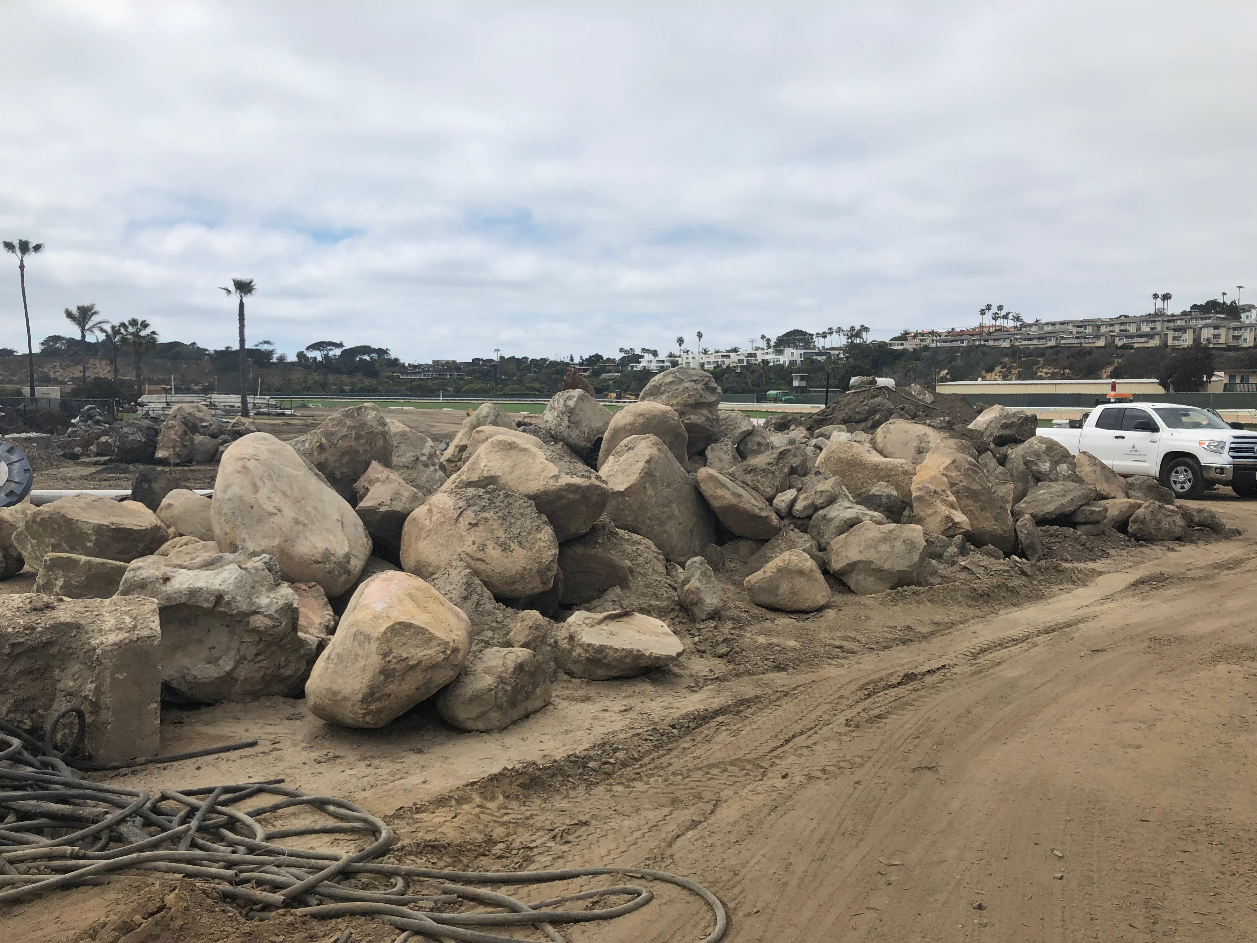 Boulders, in a long pile with a white truck in the background