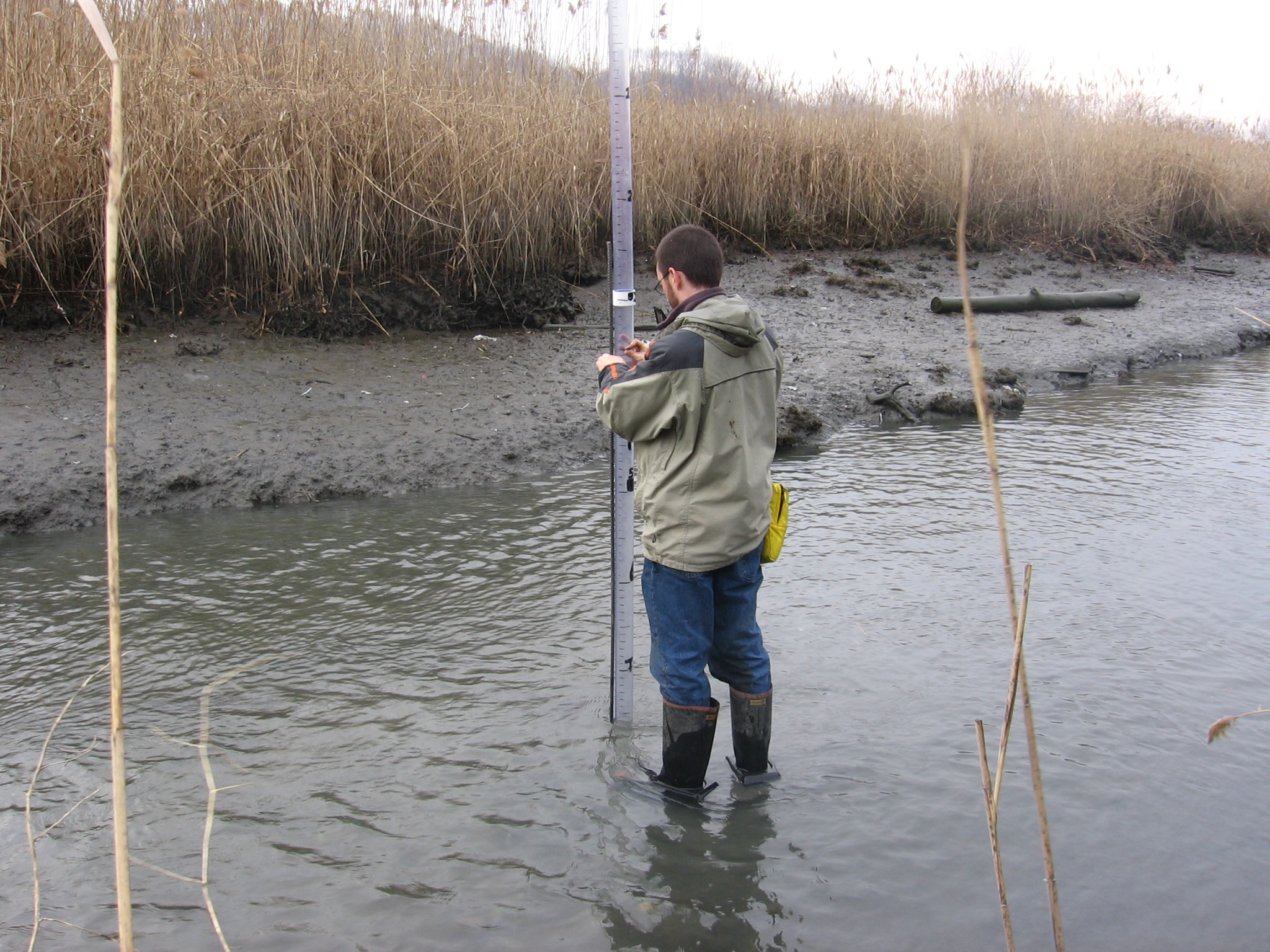 A man in boots measures stream depth