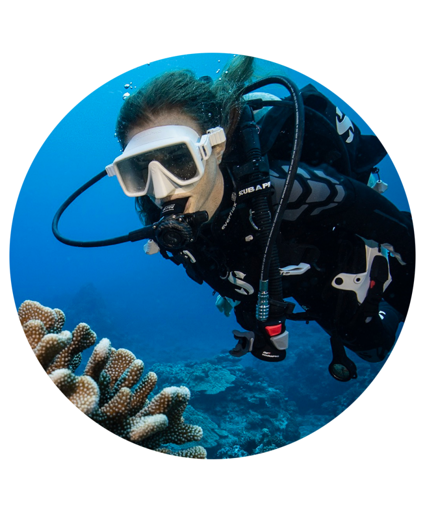 woman in scuba gear under water next to coral