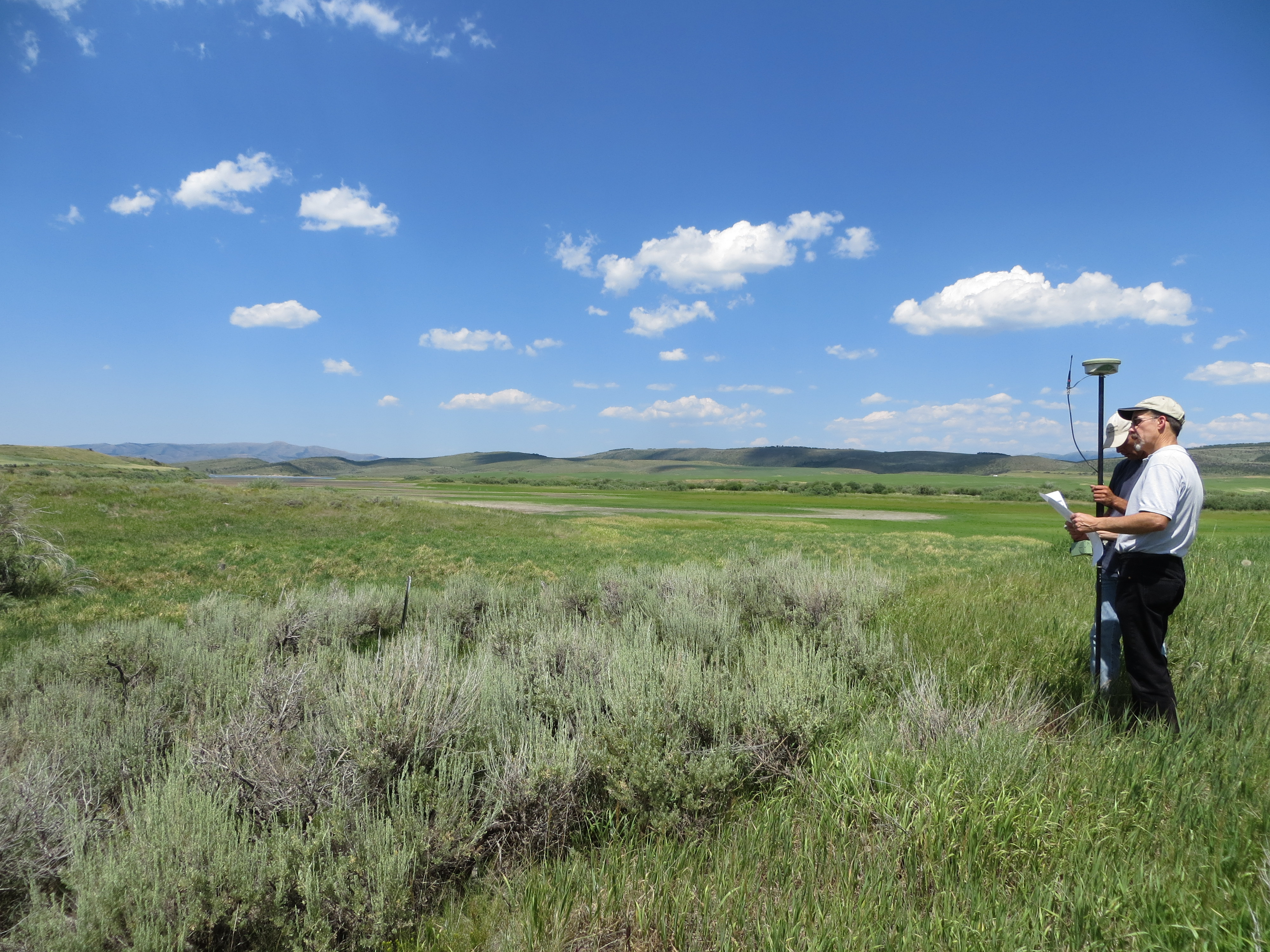 Two men stand in a field, with equipment for evaluating conditions. Sage is growing prominently in the foreground.